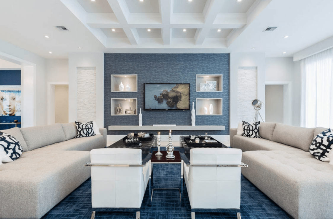 Modern living room features a coffered ceiling and a deep blue accent wall fitted with inset shelves that are filled with lovely frames and vases.