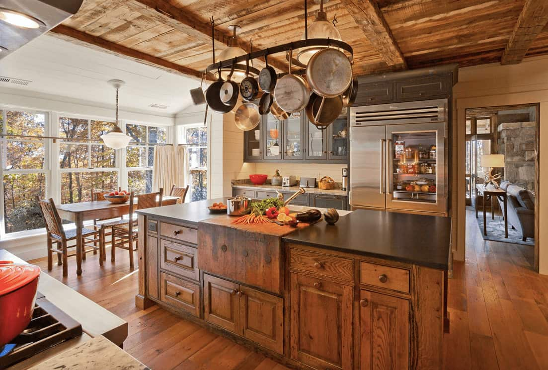 An all wood kitchen showcasing gray cupboard and glass front upper cabinetry along with a metal pot rack that hung over a natural wood breakfast island topped with a black granite counter.