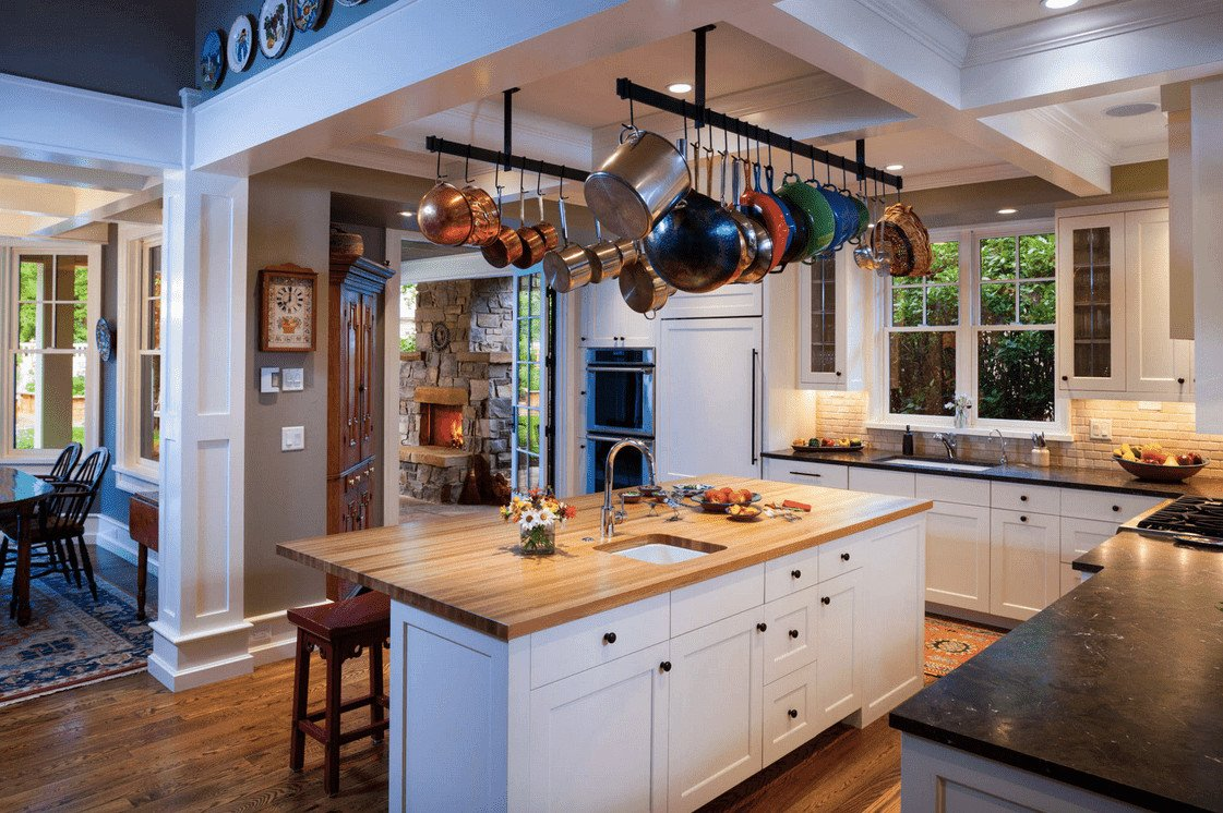 An open kitchen with white cabinetry and a pair of linear pot racks that hung from the coffered ceiling over a wooden top kitchen island.