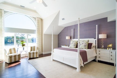 Spacious primary bedroom with hardwood flooring topped by a white rug, along with a purple wall.