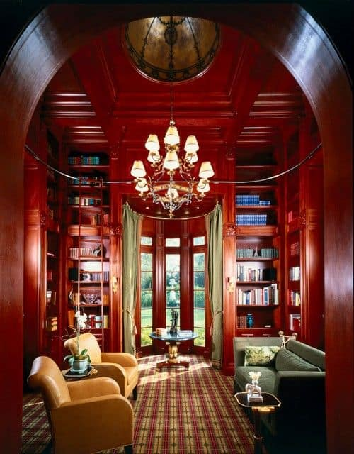 A living room library featuring multiple built-in shelves along with a pair of yellow chairs and a couch lighted by a glamorous chandelier hanging from the red coffered ceiling.