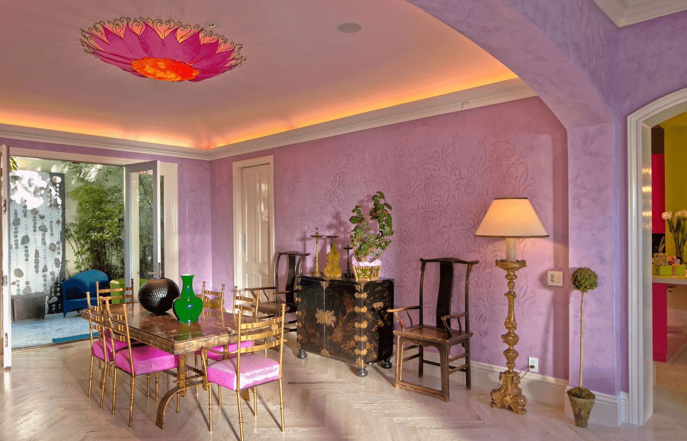 This dining room features a fancy dining table and chairs set lighted by a very attractive ceiling lighting. The area is surrounded by purple walls.