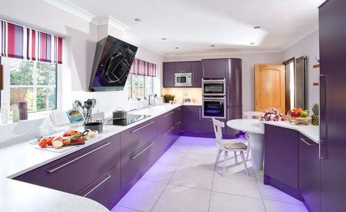 This kitchen features smooth white countertops along with white tiles flooring. The kitchen counters and cabinetry are all finished in purple.