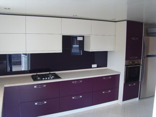 Simple kitchen setup with white and purple accent. The room features tiles flooring and a regular white ceiling.