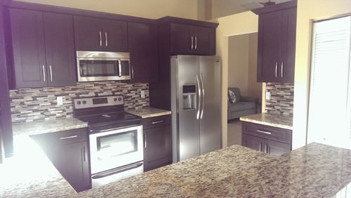Small kitchen area featuring granite countertops and purple kitchen counters and cabinetry.