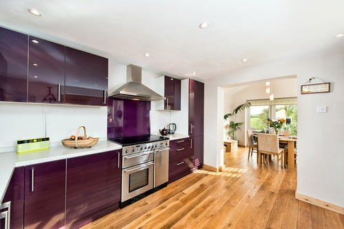 Spacious kitchen featuring hardwood floors and white walls, along with a purple accent on the cabinetry and kitchen counters.