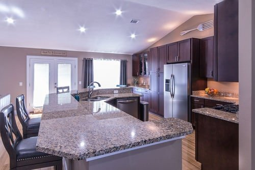 Spacious kitchen featuring a large island with a breakfast bar and has granite countertops. The vaulted ceiling is lighted by recessed lights.