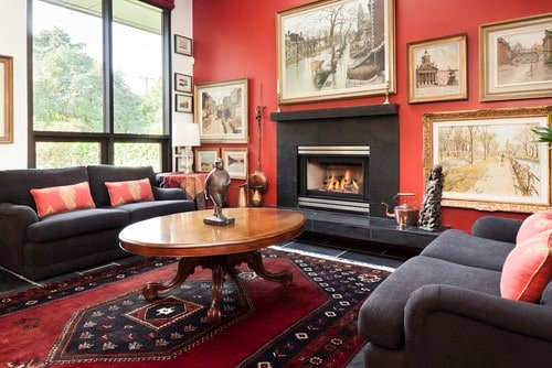This living room offers dark gray seats and a black fireplace, along with a very stylish rug covering the black tiles flooring.