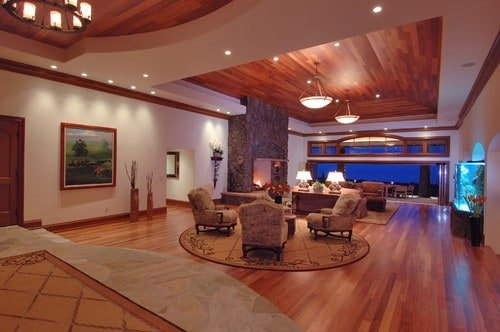 Huge formal living room with hardwood flooring that matches the ceiling. The seats look so elegant together with the large fireplace.