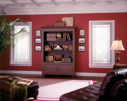 A spacious living room with a freestanding bookshelf surrounded by red walls.