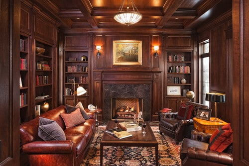 An elegant living room with brown leather seats, a fireplace and multiple bookshelves filled with books.