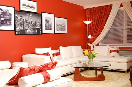 This living room offers a set of white seats surrounded by red walls with a few framed wall decors.