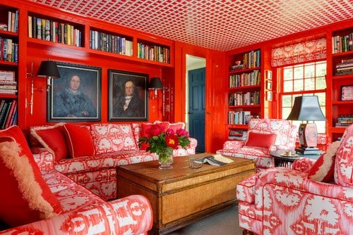 A small living space featuring red walls and red accent seats. The ceiling also has a charming look. The room is filled with books in multiple bookshelves.
