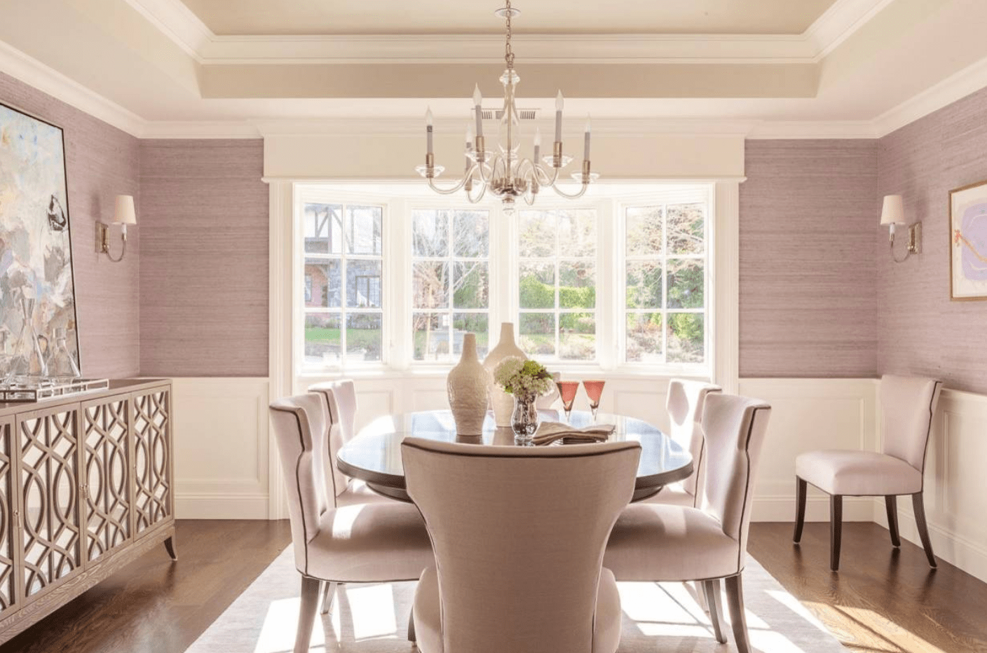 A bright dining room featuring a cozy dining table and chairs set. The room features pink walls with wall sconces. The area is lighted by a gorgeous chandelier.