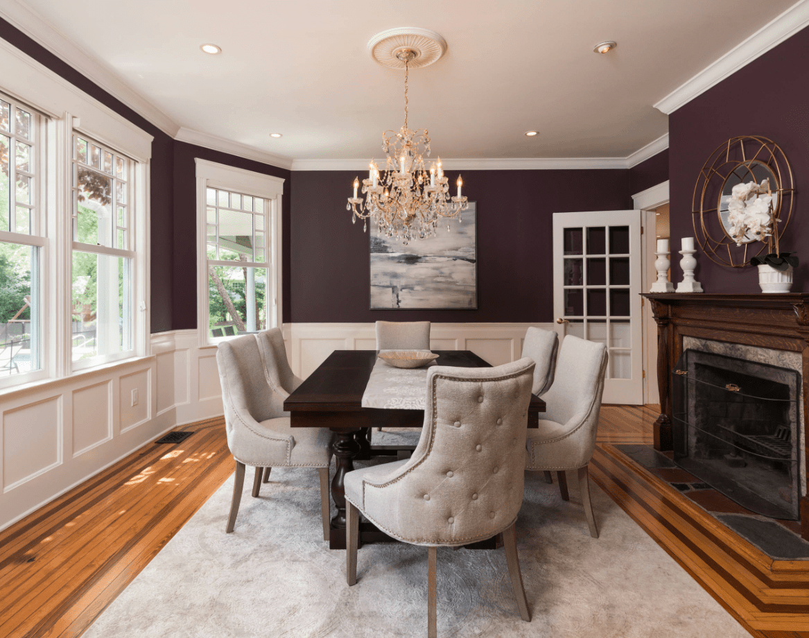 This dining room features hardwood flooring topped by a large gray rug. The room also has a large fireplace, classy table and chairs set, purple walls and a glamorous chandelier.