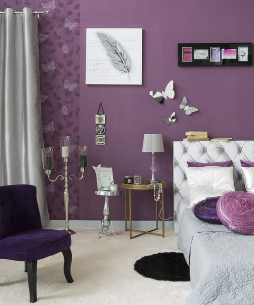 Master bedroom with a luxurious-looking bed frame, a gold-finished side table with a silver lamp on top and cute wall decors on the purple walls. The room also has carpet flooring.