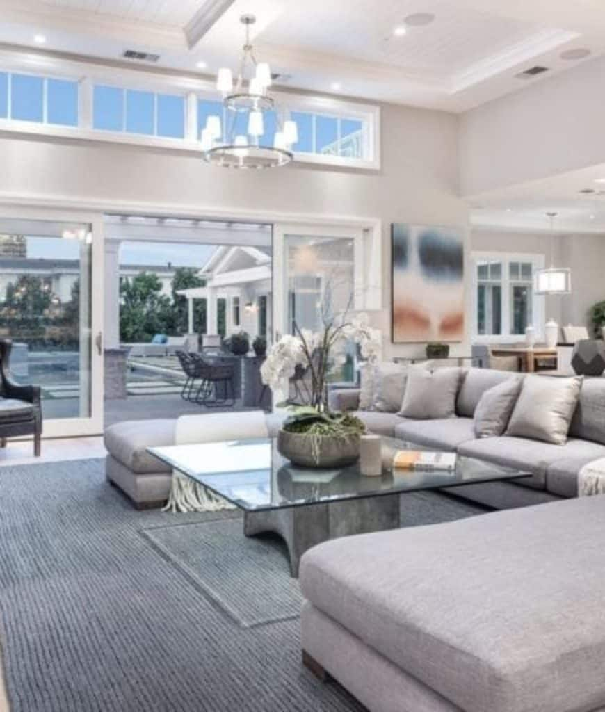 Open concept living room features gray sectional and a glass top coffee table lighted by a two-tier chandelier that hung from the coffered shiplap ceiling.