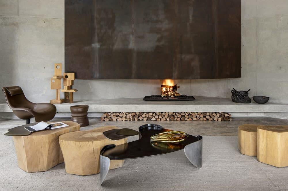 This is a charming and cozy Industrial-style living room by the large fireplace that is against a large gray concrete wall matching the ledge that serves as a fire wood storage and the gray area rug that makes the mirrored coffee table stand out as well as the wooden stumps for sitting.