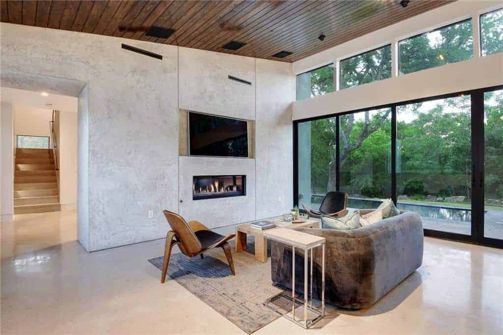 The high wooden shed of this industrial-style living room is augmented by a large glass wall with glass sliding doors that show a nice scenery outside with a pool. This serves as a nice background for the gray velvet sofa facing a simple rustic wooden coffee table and a fireplace that is embedded into a gray concrete wall.