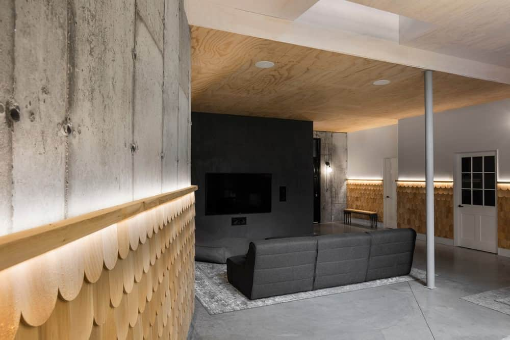 This simple living room has a dark gray sectional sofa facing a matching dark gray wall that supports the wall-mounted TV and its sound system. These gray elements stand out against the bare wooden ceiling that matches the bare wooden wainscoting with a textured scales design on it.