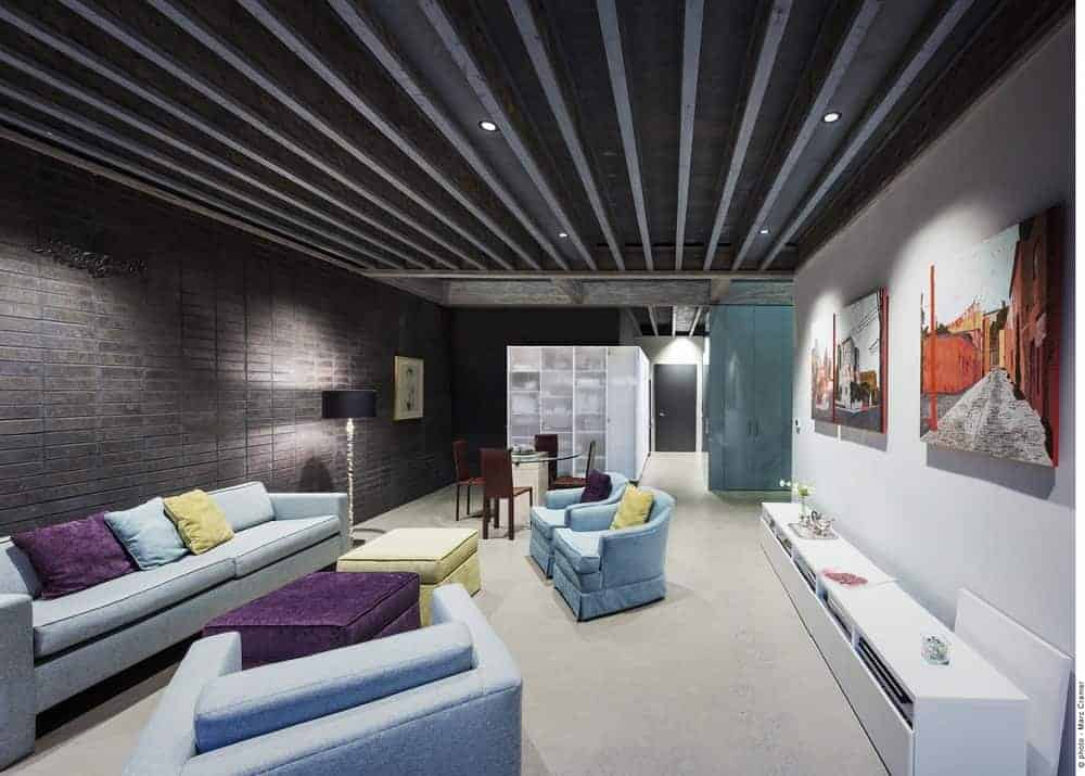 This living room has a wide ceiling filled with dark gray metal beams with recessed lights that complements the dark gray stone walls that contrast the light blue sofa set facing the concrete wall adorned with colorful paintings.