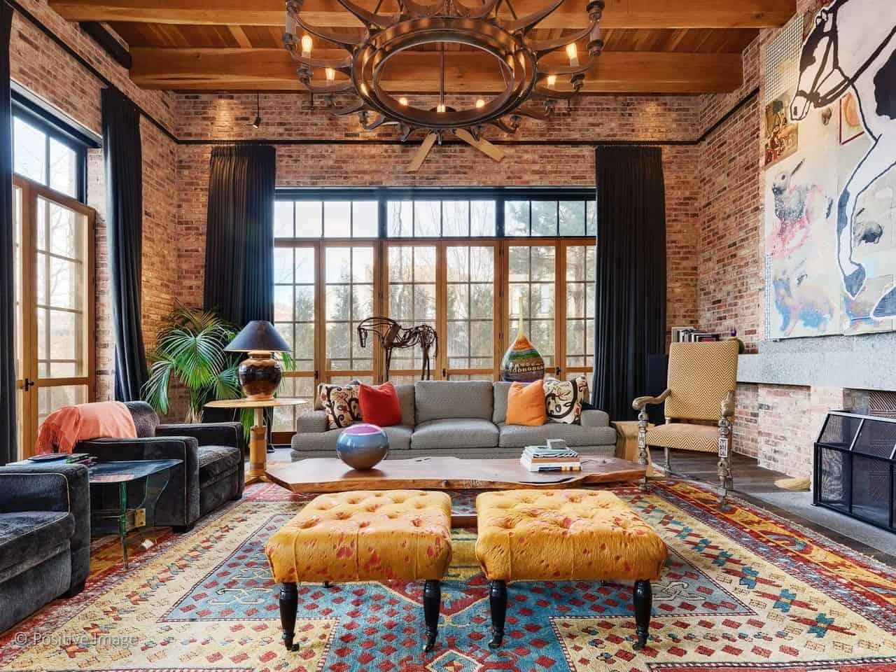 The wooden ceiling with large exposed wooden beams are a perfect match for the brick walls surrounding this industrial-style living room that has a large gray couch facing a rustic coffee table in the middle of a colorful patterned area rug.