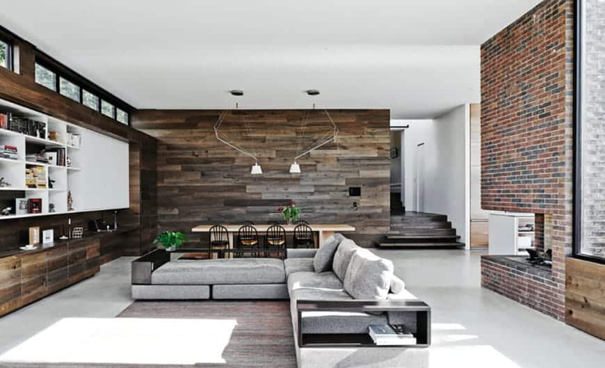 Behind the light gray L-shaped sectional sofa has a fireplace inlaid with a large column of red bricks. In front of the sofa is a large wooden structure that is embedded into the wall that houses cabinets and shelves filled with decors.