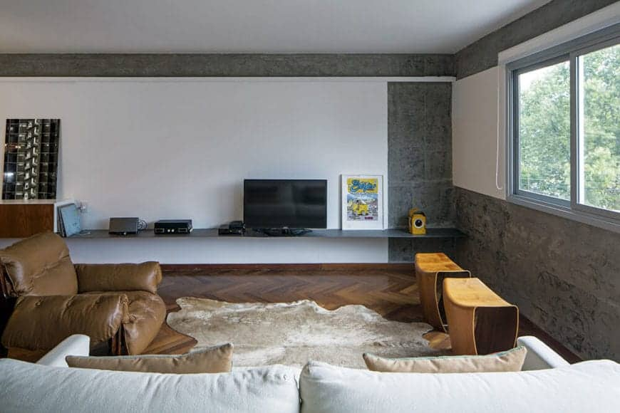 This simple living room has a brown leather cushioned armchair that matches with the hardwood flooring with a herring bone pattern. This is contrasted by the white walls accented with sections of gray concrete.