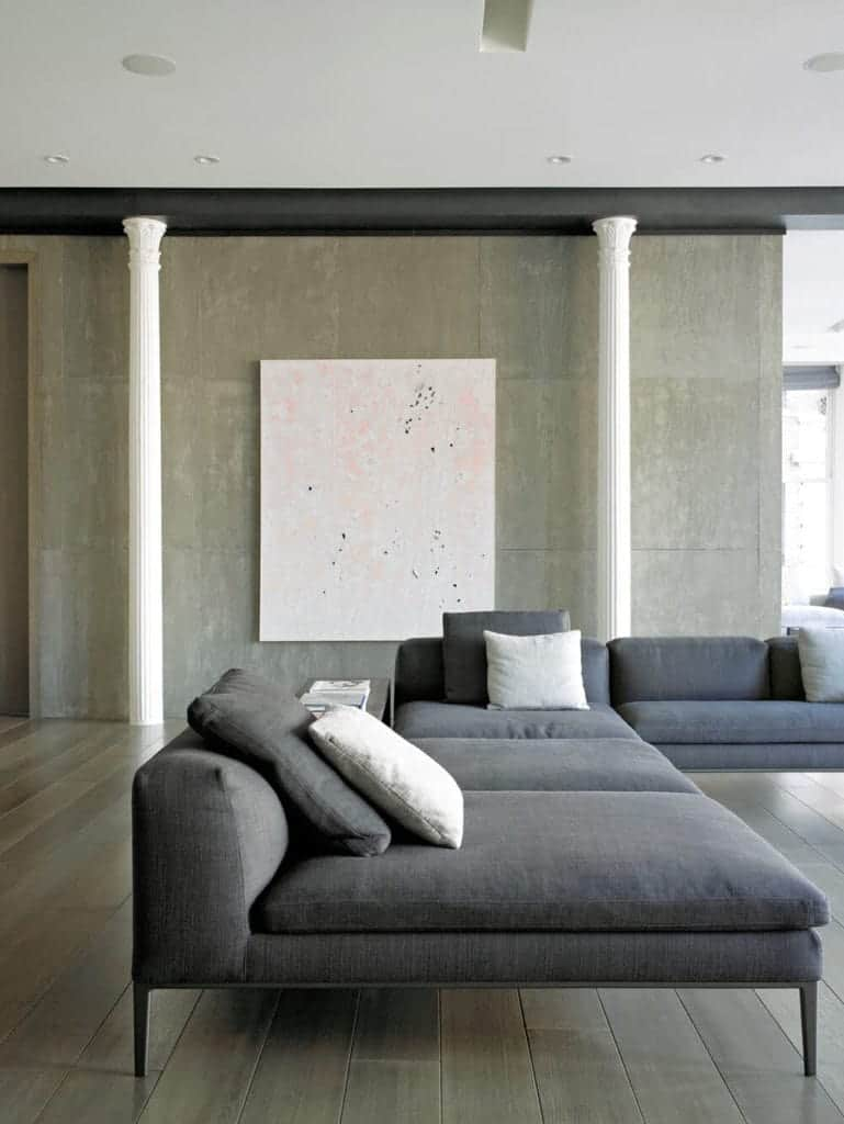 The large gray L-shaped sectional sofa has thin dark wooden legs that complement the hardwood flooring that has a dark gray hue to it matching well with the concrete gray walls that are contrasted by the thin white pillars and artwork.