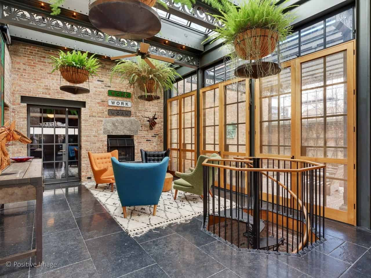 The brightness of this industrial-style living room is due to its glass ceiling with exposed metal beams that has multiple hanging potted plants. It is also due to the glass doors adjacent to the red brick wall that has a fireplace.