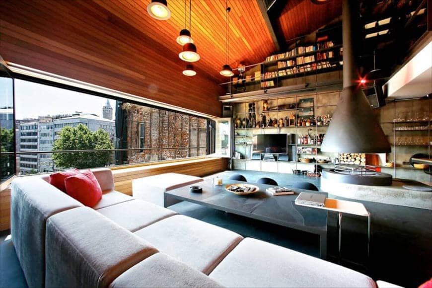 The wooden shed ceiling has a redwood shiplap finish to it that extends to the wall that is dominated with a wide and narrow open space thanks to folding glass windows. This brings in natural lights to the light cushioned sofa and the dark flooring.