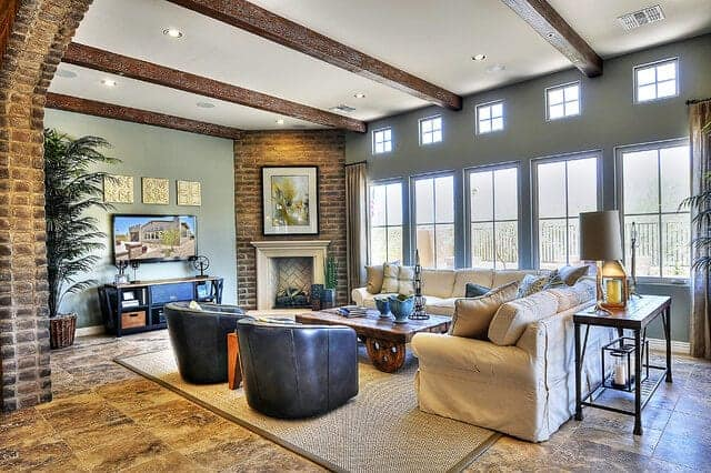 The bright row of windows on one side of this living room brings in an abundance of natural lighting to the white ceiling and its exposed wooden beams as well as the adobe bricks of the fireplace and the arched entryway.