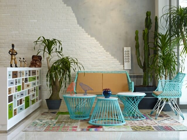 This industrial-style living room has a cheery demeanor thanks to the light green set of furniture over a colorful patterned area rug. This is given a background of gray concrete that fades into a white stone wall.