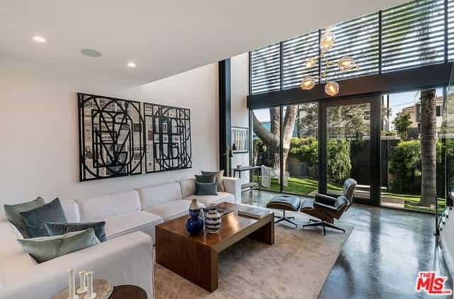 This simple white living room has an industrial-style background of the large glass wall of the entrance to this home. It has metal frames in a dark hue that stands out against the brightness of the natural lights and the nice landscaping outside.