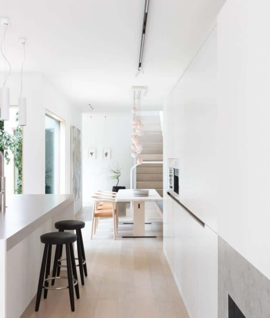 Bright dine-in kitchen with a galley layout. It showcases a sleek breakfast bar paired with black stools along with a white dining table and round back chairs.