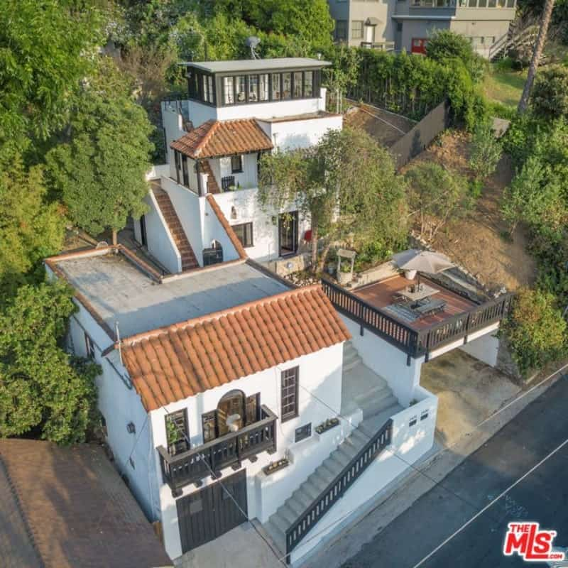 This Spanish home maximizes its small lot with its utilization of the vertical space. It also follows the sloped lay of the land with the use of stone stairways leading to different section levels of the house. The modern style of the highest level stands out against the traditional parts, yet it doesn't clash but adds to the aesthetic instead.