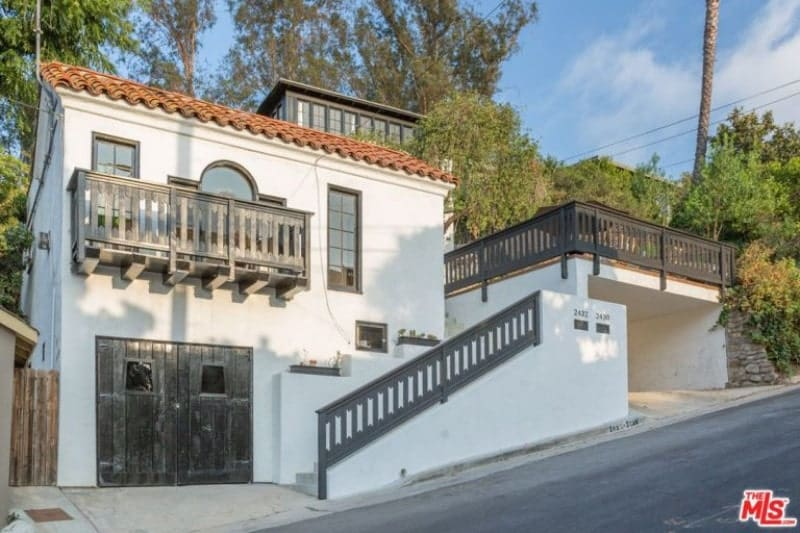 A Spanish-style home that is predominantly white which provides a good background for the grayish wooden main doors, clay-tiled roof, and stair railing. An elegant wooden balcony supported by wooden beams is placed above the main doors with French windows.