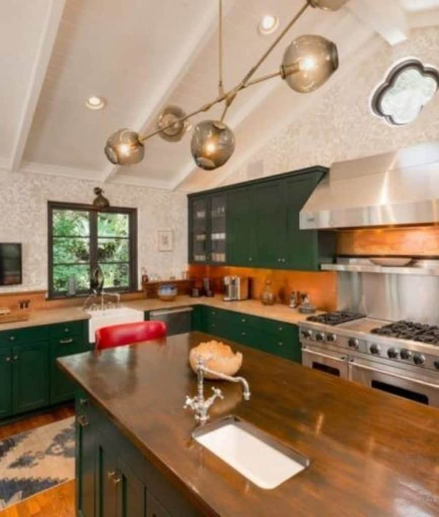 Charming kitchen with cathedral ceiling and rich hardwood flooring topped by a kitchen runner. It has a wooden breakfast island and stainless steel range with hood next to the green cabinetry.