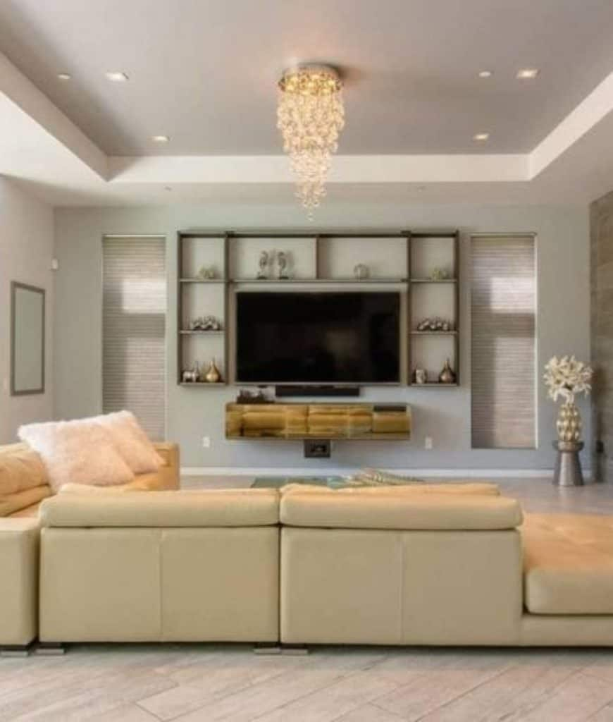 Fabulous living room with cream sectional and flat panel TV surrounded with open shelving. It includes wood plank flooring and tray ceiling with a hanging crystal chandelier.