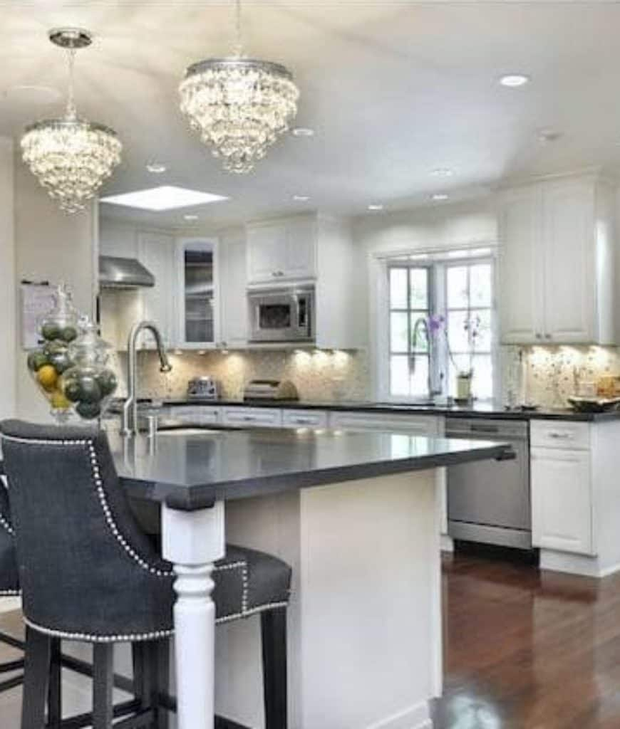 Transitional kitchen features white cabinetry and a granite top kitchen island paired with gray upholstered chairs and lighted by fancy chandeliers.