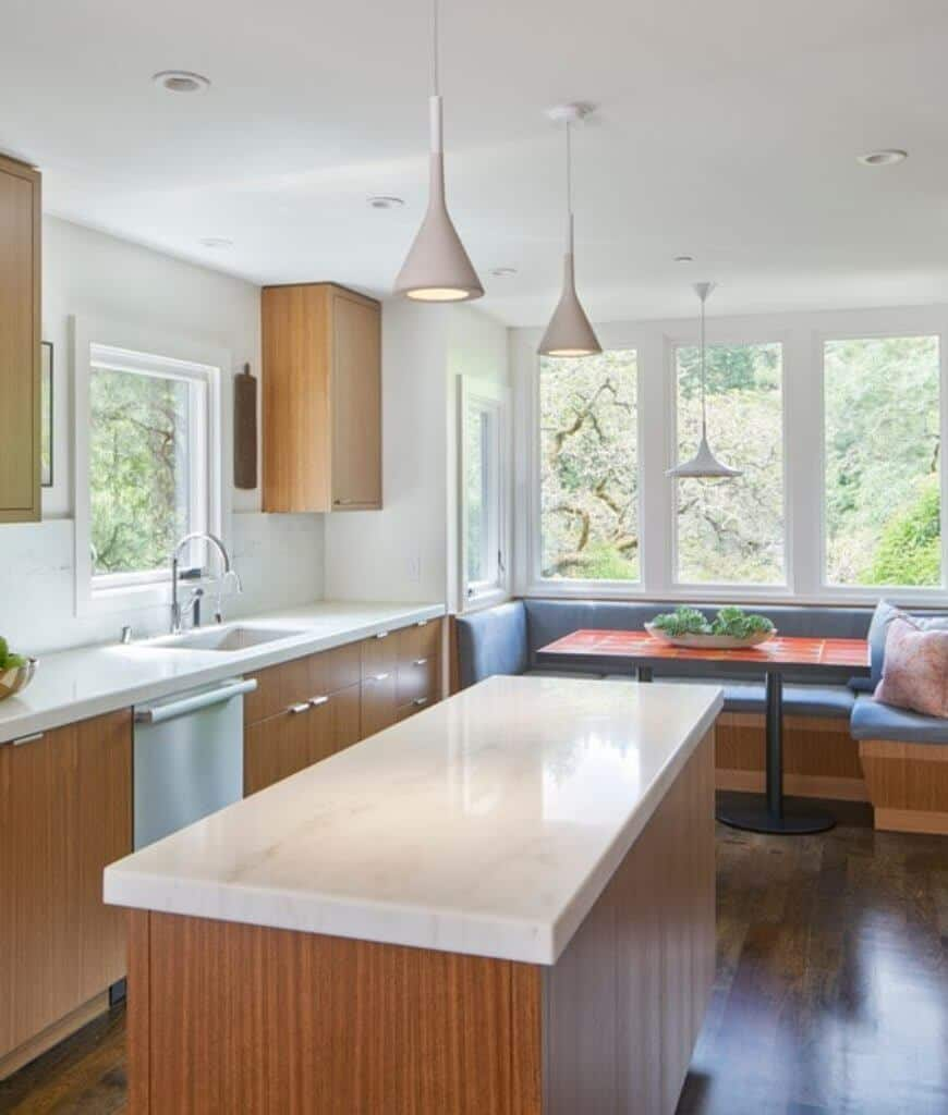 Airy kitchen boasts sleek white pendants and wooden cabinetry that matches with the central island bar. It includes a breakfast nook fitted with blue sectional cushions and paired with a metal dining table.