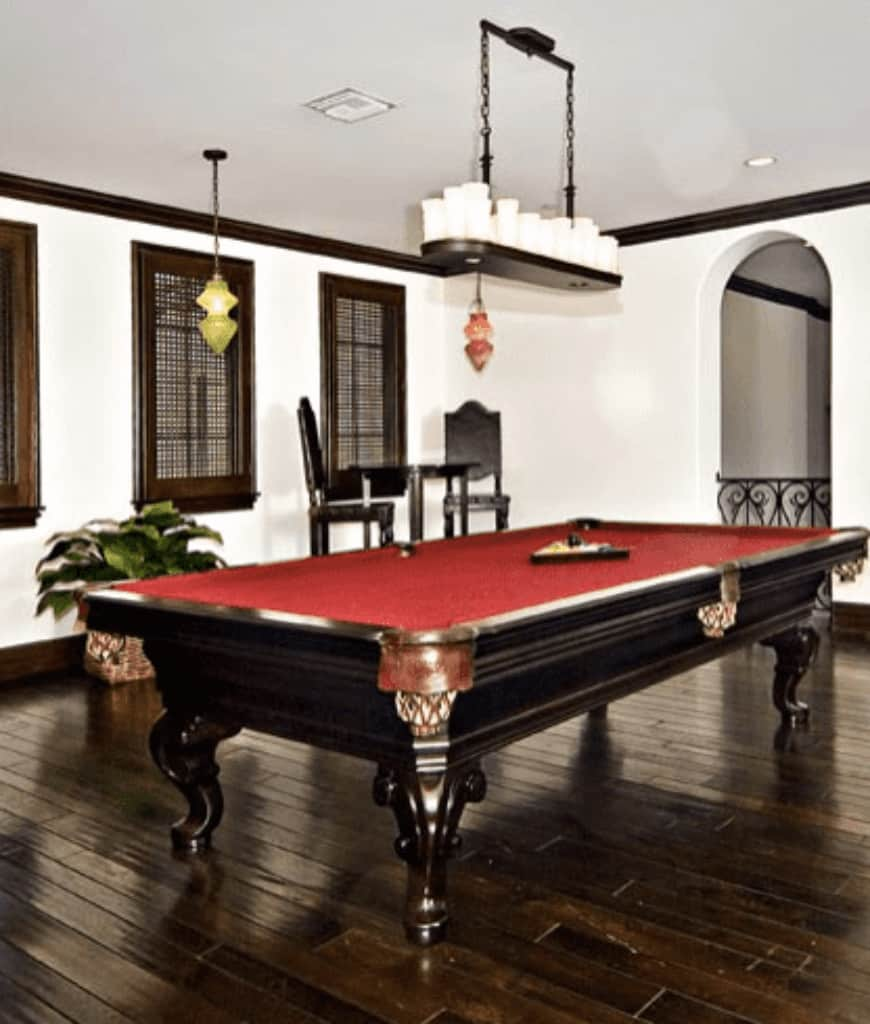 Classic white room features a red pool table lighted by a linear chandelier and accompanied with black bar chairs by the wooden framed windows.