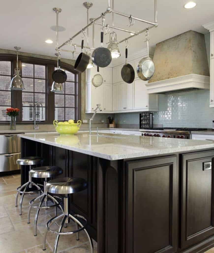 Stainless steel pot rack hangs over the dark wood breakfast island that's lined with chrome counter chairs in this kitchen with white cabinetry and concrete range hood fixed to the soft blue backsplash tiles.