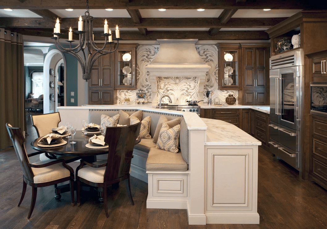 An all wood kitchen with a dining nook fixed to the white marble top island bar featuring a round dining table and wingback chairs.