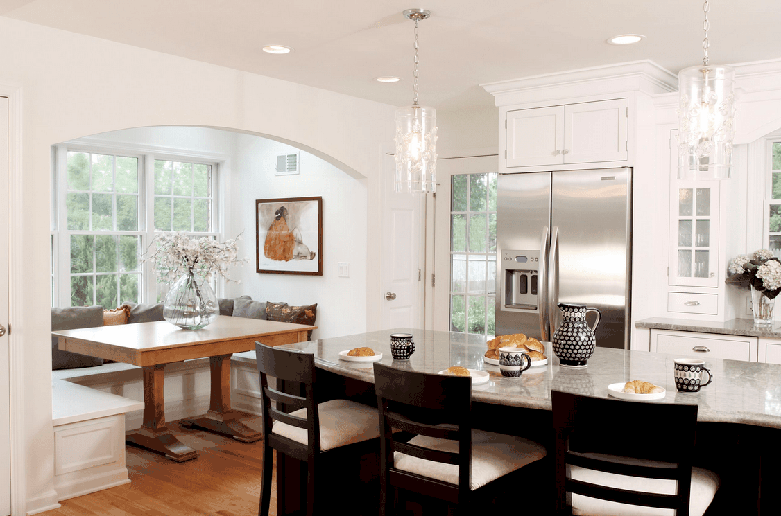 An alcove dining nook boasts a wooden dining table and built-in seating filled with neutral pillows. It faces the dark wood breakfast island lighted by fancy glass pendants.