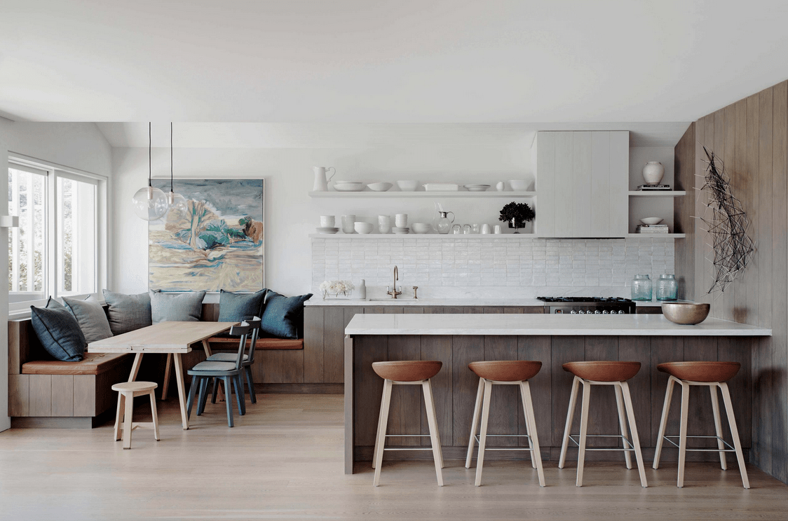 This kitchen offers a wood plank peninsula that matches with the cupboard and built-in seating of the dining nook. It is lighted by a pair of glass globe pendants that hung over the wooden dining table.