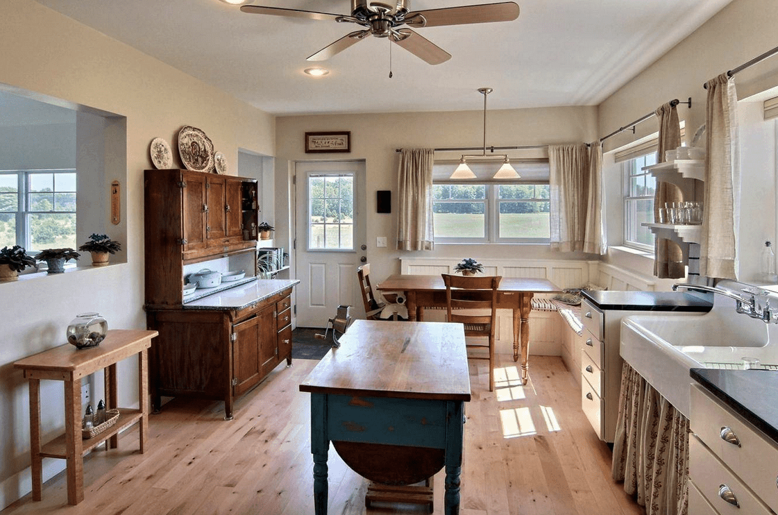 An eat-in kitchen with a dining nook by the glass windows featuring white beadboard seating and a wooden dining table with matching chairs.