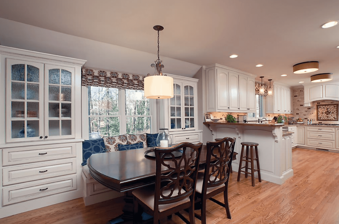 A cozy dining nook across the two-tier peninsula and in between display cabinets. It has a built-in seating accented with blue patterned pillows and a wooden dining table with ornate cushioned chairs.
