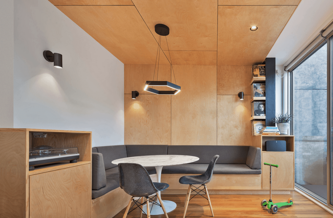 A hexagonal pendant light illuminates this dining nook along with black sconces mounted on the wooden paneled walls. It has a built-in seating fitted with gray cushions that complements with the modern chairs.