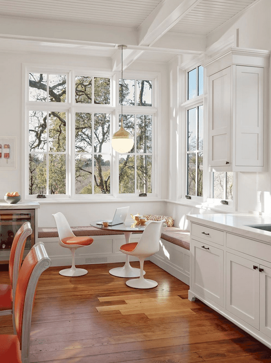 An airy dining nook showcases an L-shaped seating and a round dining table with orange cushioned chairs that sit on wood plank flooring.